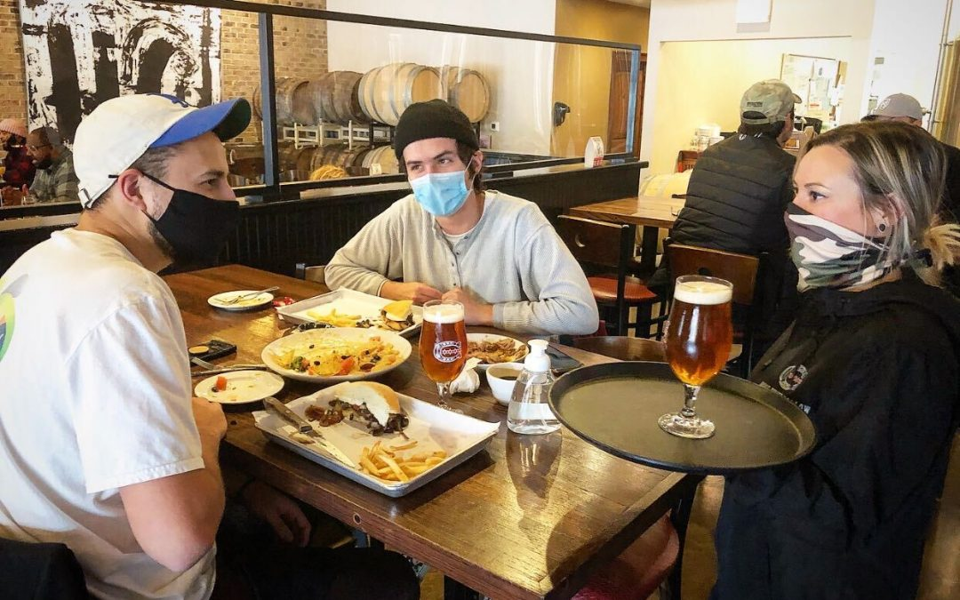 Horse Thief Hollow shows server and two customers interacting safely, wearing masks, and using hand sanitizer